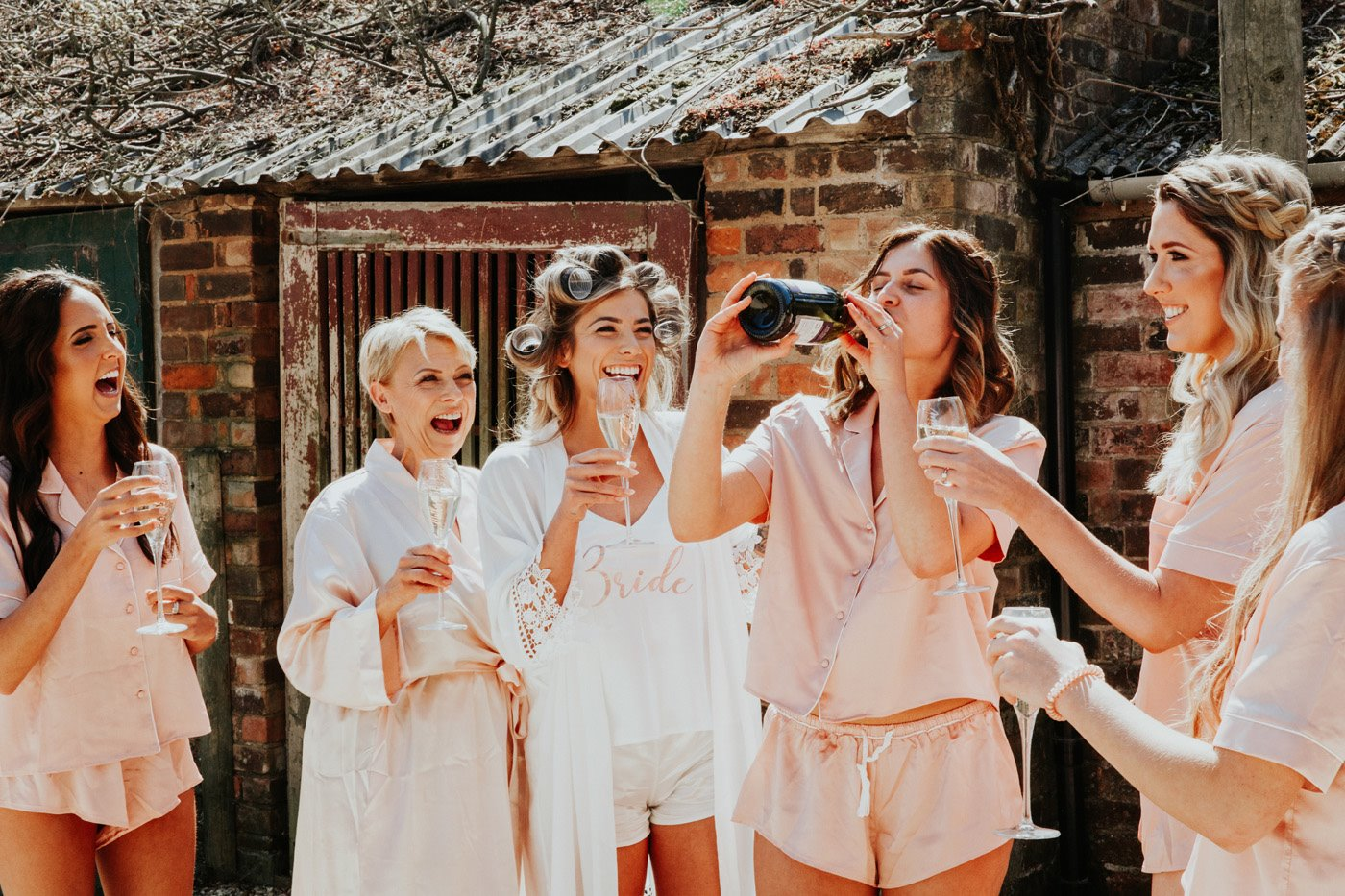 Bridal party in pink and white robes and pyjamas laugh as the bride drinks prosecco out of the bottle