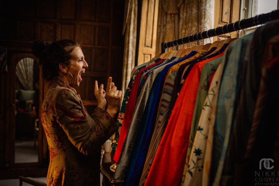 Shibumi founder Ruth excitedly holds fingers up to a rail of cashmere jackets at a wedding fair in Gloucestershire