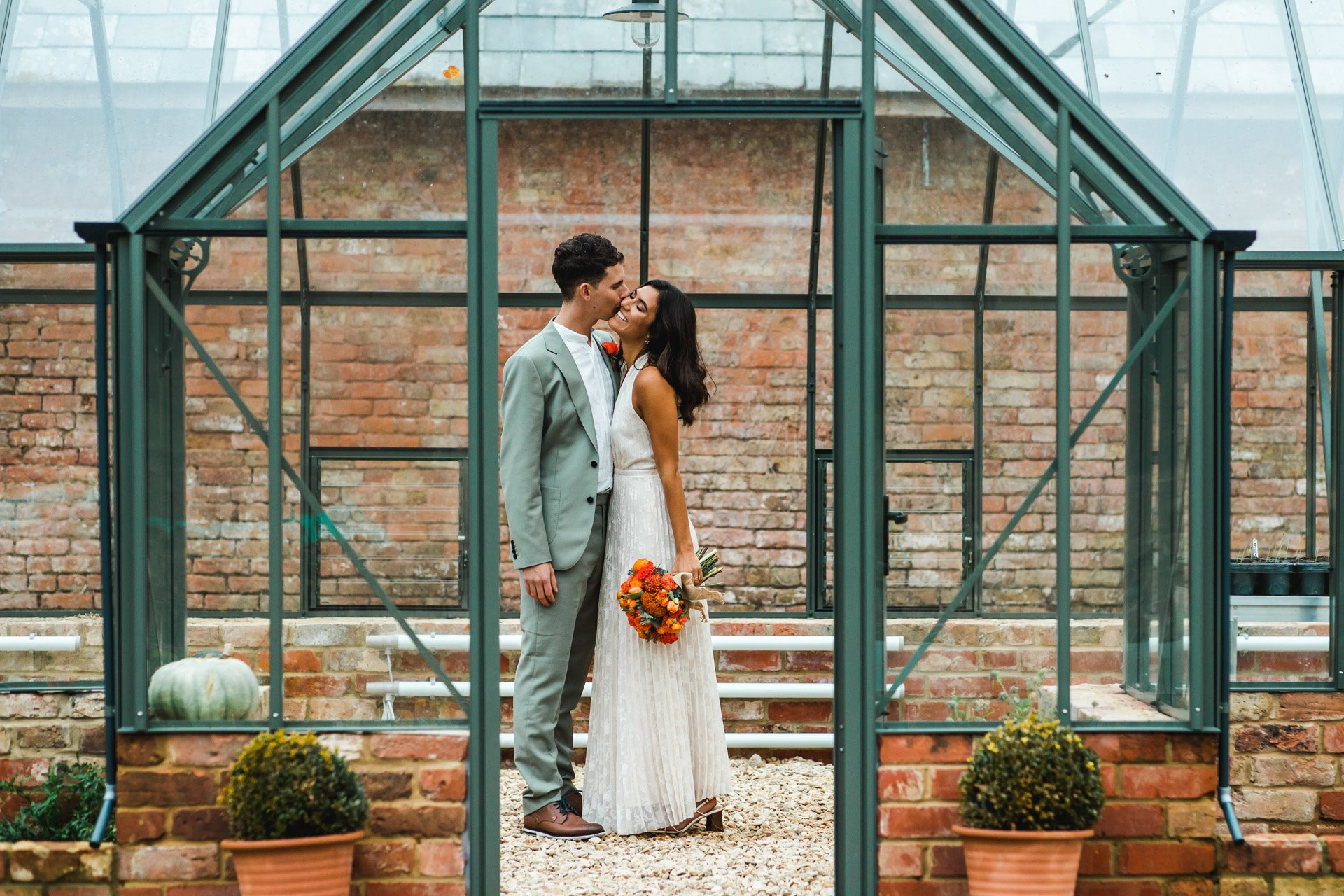 Bride and groom kiss in a glasshouse at a micro wedding at elmore court