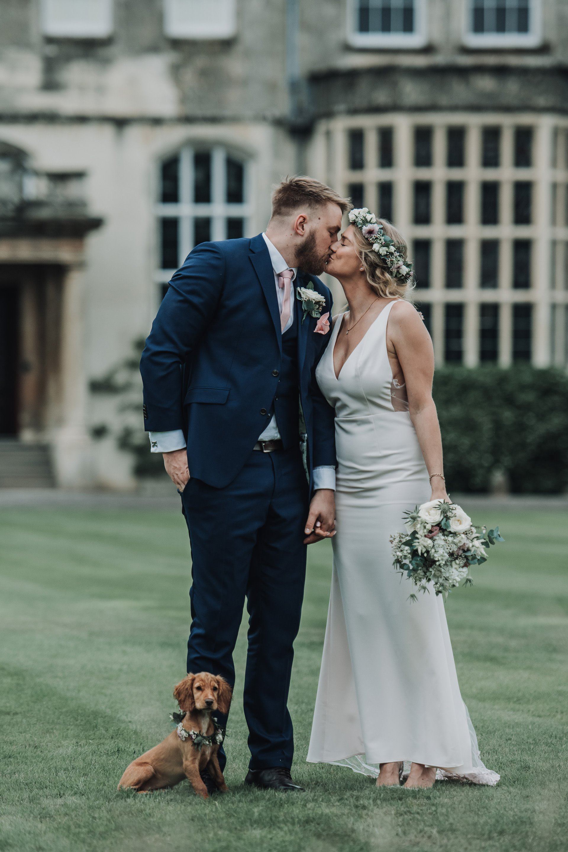 Dog friendly micro wedding at Elmore court. Bride and Groom kiss on the lawn in front of stately home with their puppy bridesmaid dressed in flowers beside them