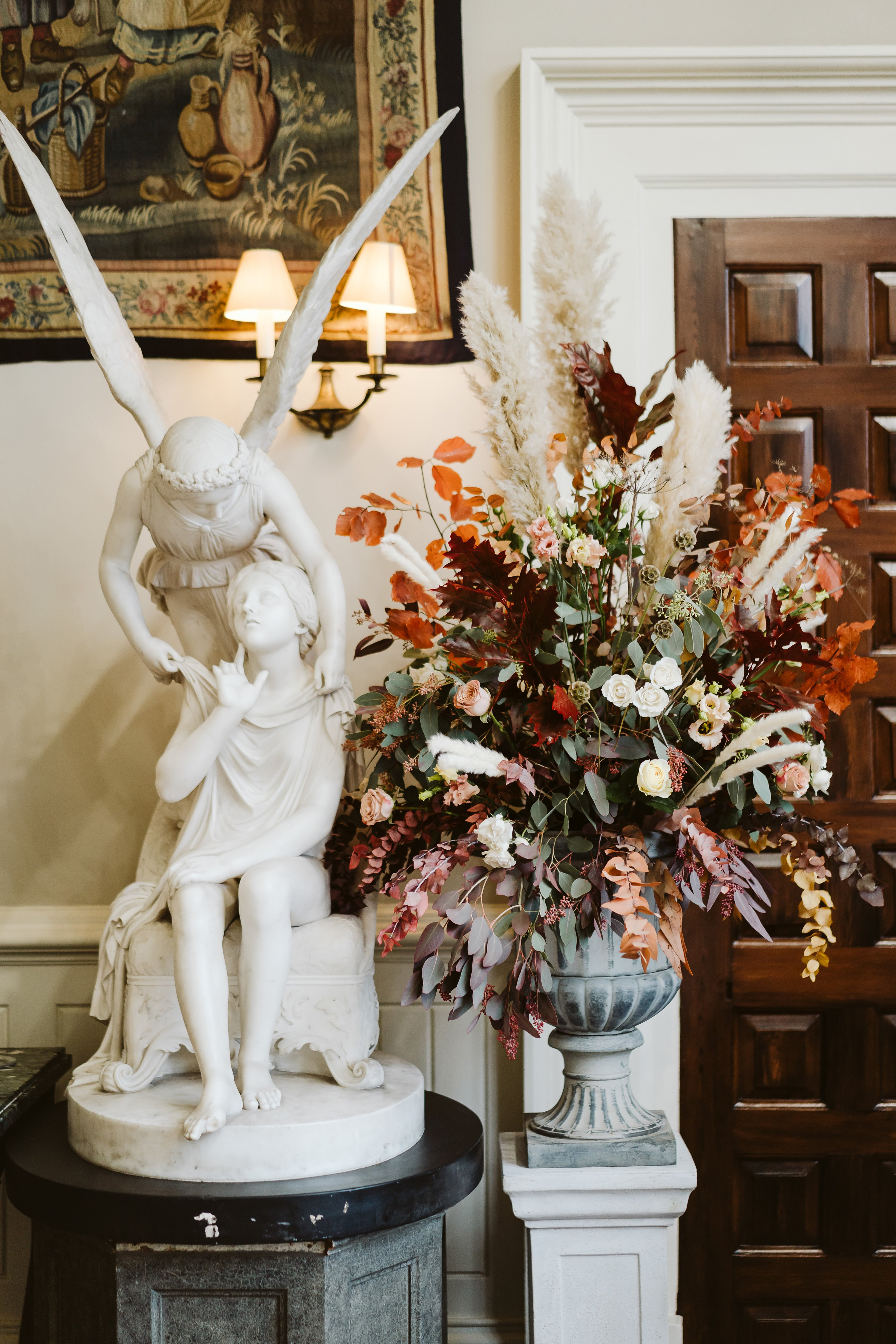 Autumn wedding at Elmore court with beautiful rustic floral arrangement in reds and oranges next to angel statue in the hall