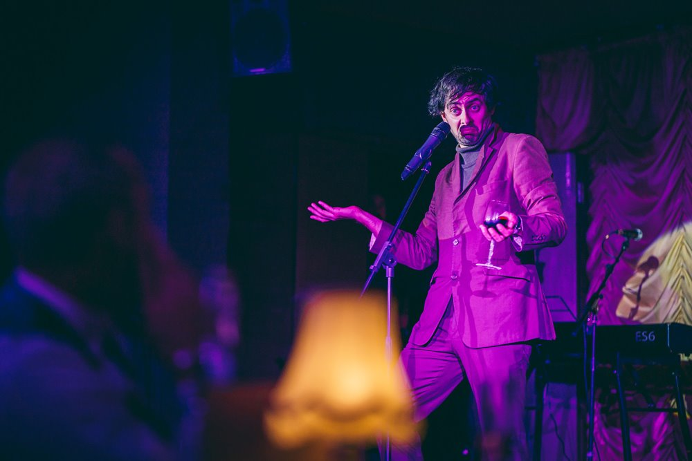 Marcel Lucount stand up comedy in purple at The Parrot Cage cabaret dinner night at elmore court 2020