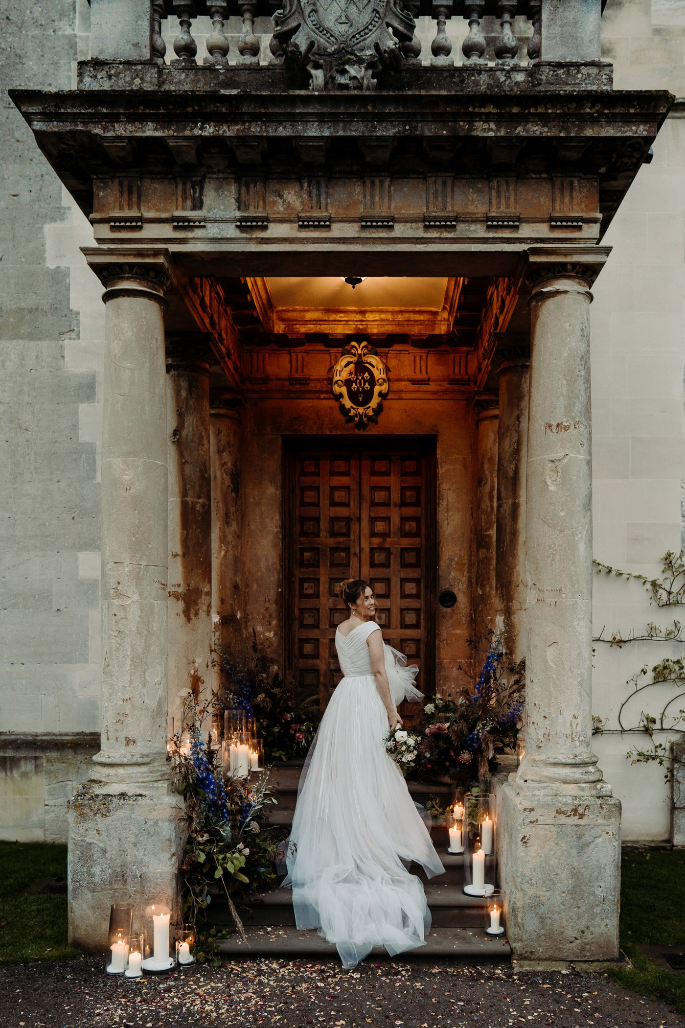 Bride stands on the entrance portico of Elmore Court with her long white gown trailing down the steps. Candles and flowers decorate either side of her