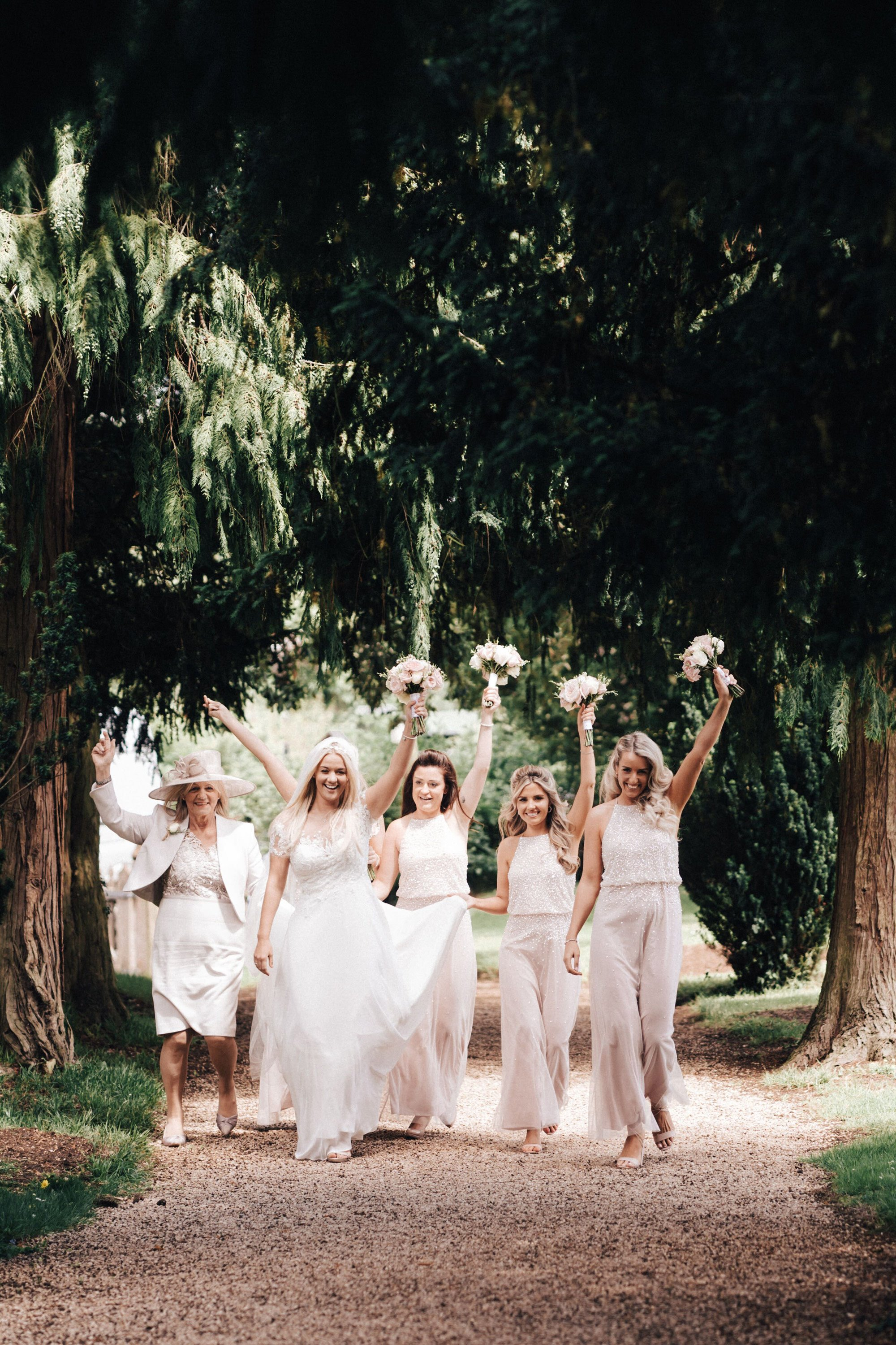Bridesmaids in pale pink holding bouquets above their heads make their way along the tree lined path to Elmore church for the wedding