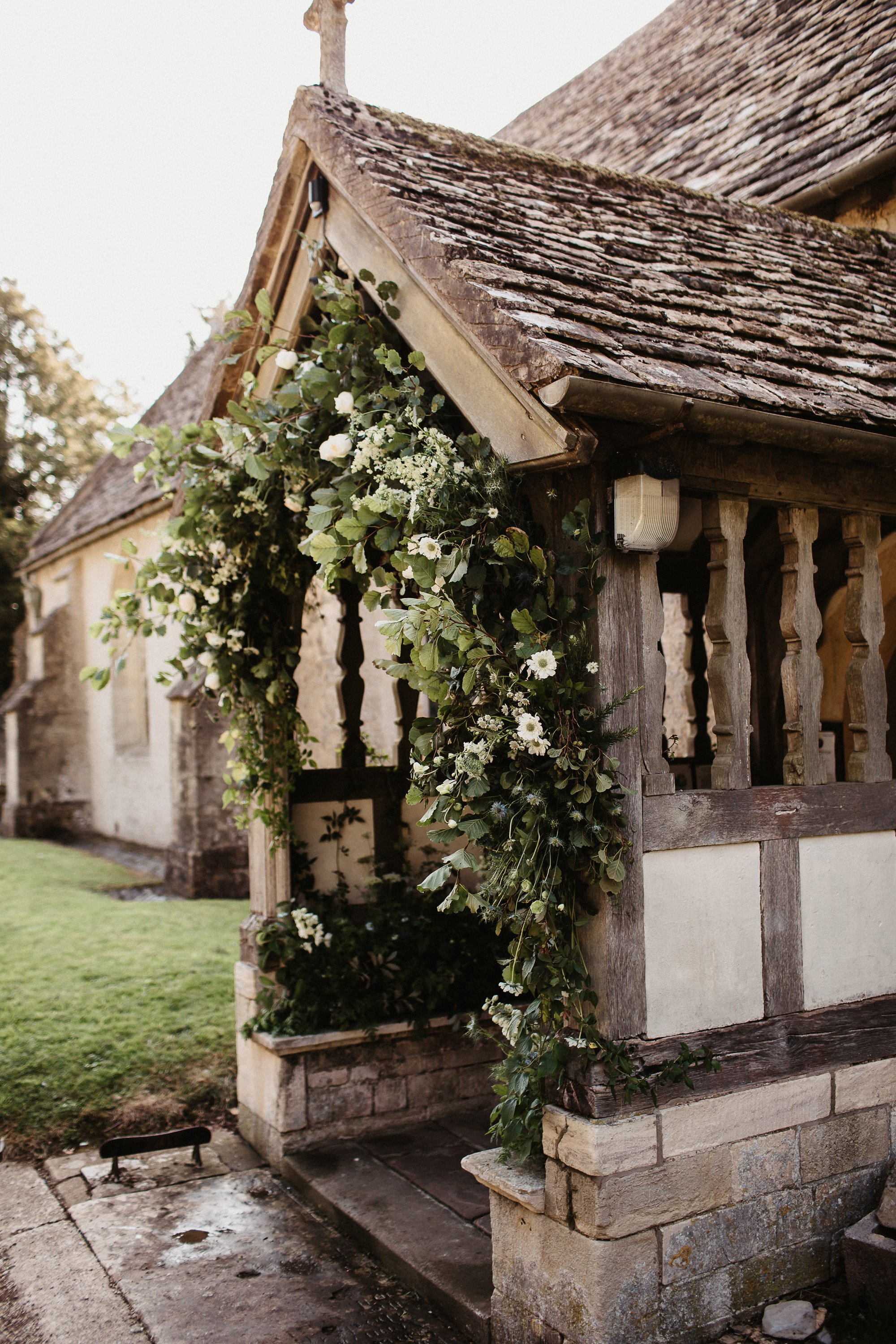 15th century English church porch at Elmore decorated with foliage and flowers for a wedding