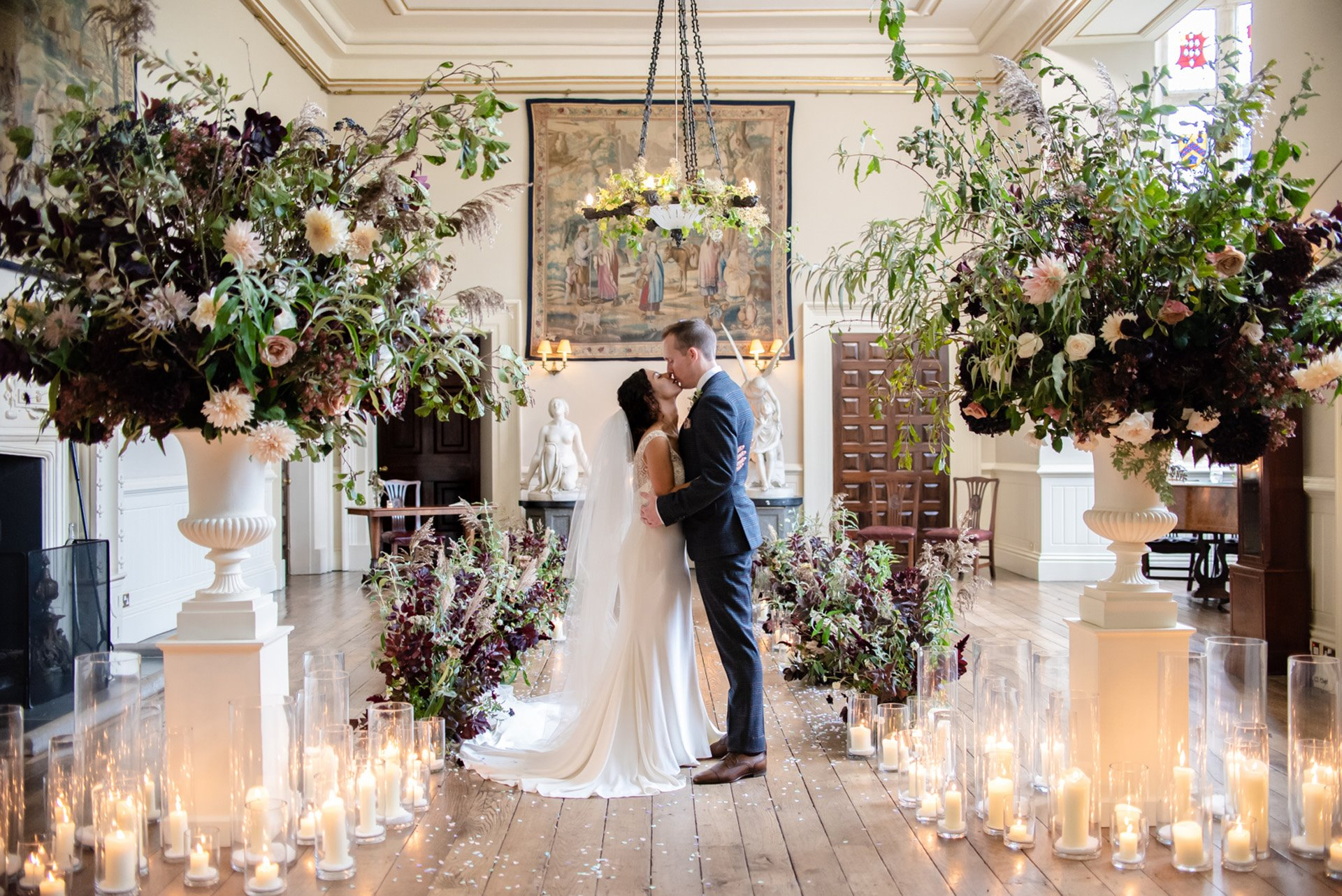Bride and groom kiss at their micro wedding with mega styling surrounded by candles, foliage and flowers