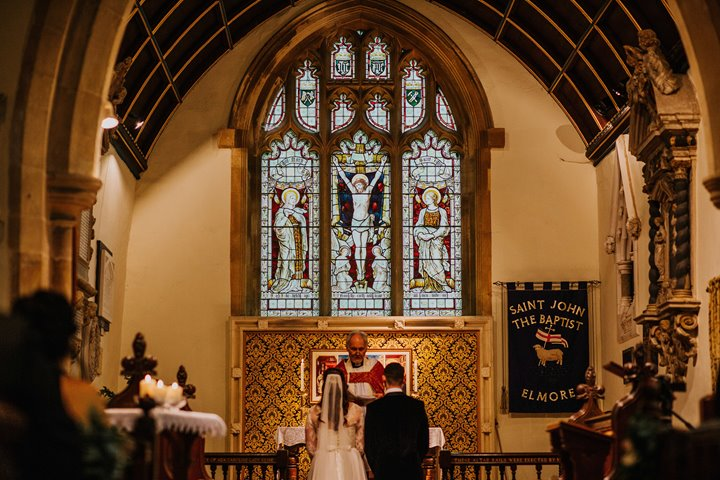 Couple and Vicar in midst of wedding ceremony at the stunning Elmore church in England with high ceilings, stained glass windows and gold details