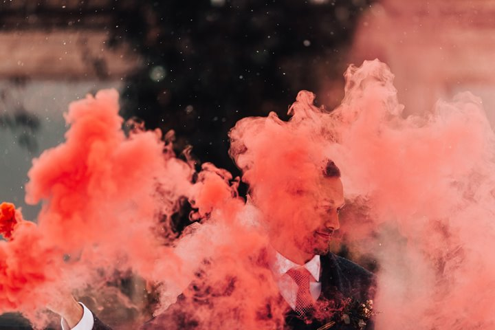 Coral coloured smoke from a smoke bomb obscures part of grooms face in a beautiful cloud of bright colour