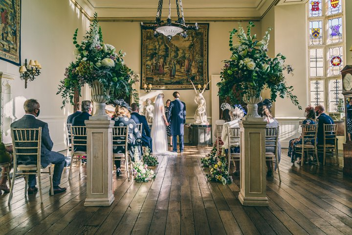 Micro wedding with big styling. Urns full of foliage and flowers flank the wedding aisle in stately home where a small number of guests watch bride and groom marry