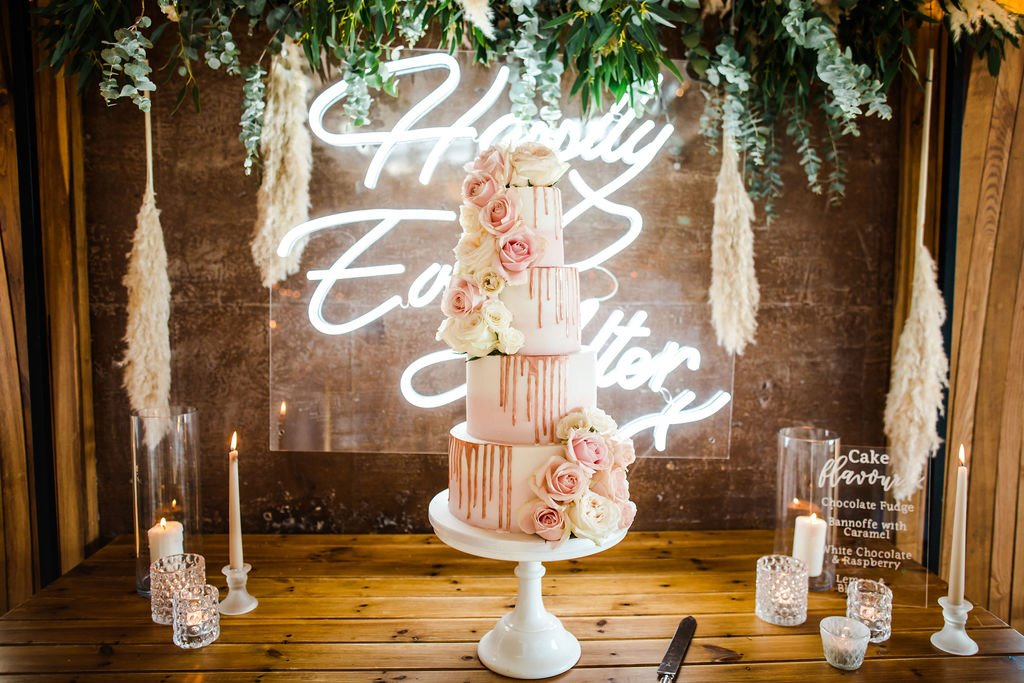 Four tier asymmetric pink wedding cake decorated with real flowers, beautifully presented on a cake table with neon sign saying happily ever after and greenery and pampas grass hanging above