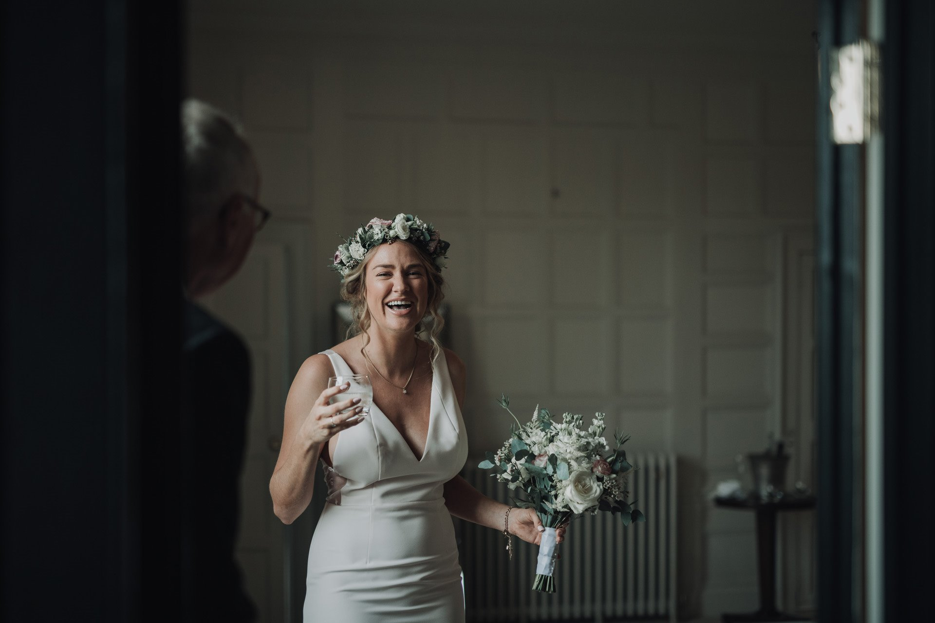 Happy bride laughs with bouquet and champagne wearing a flower crown on her micro wedding day during corona virus pandemic