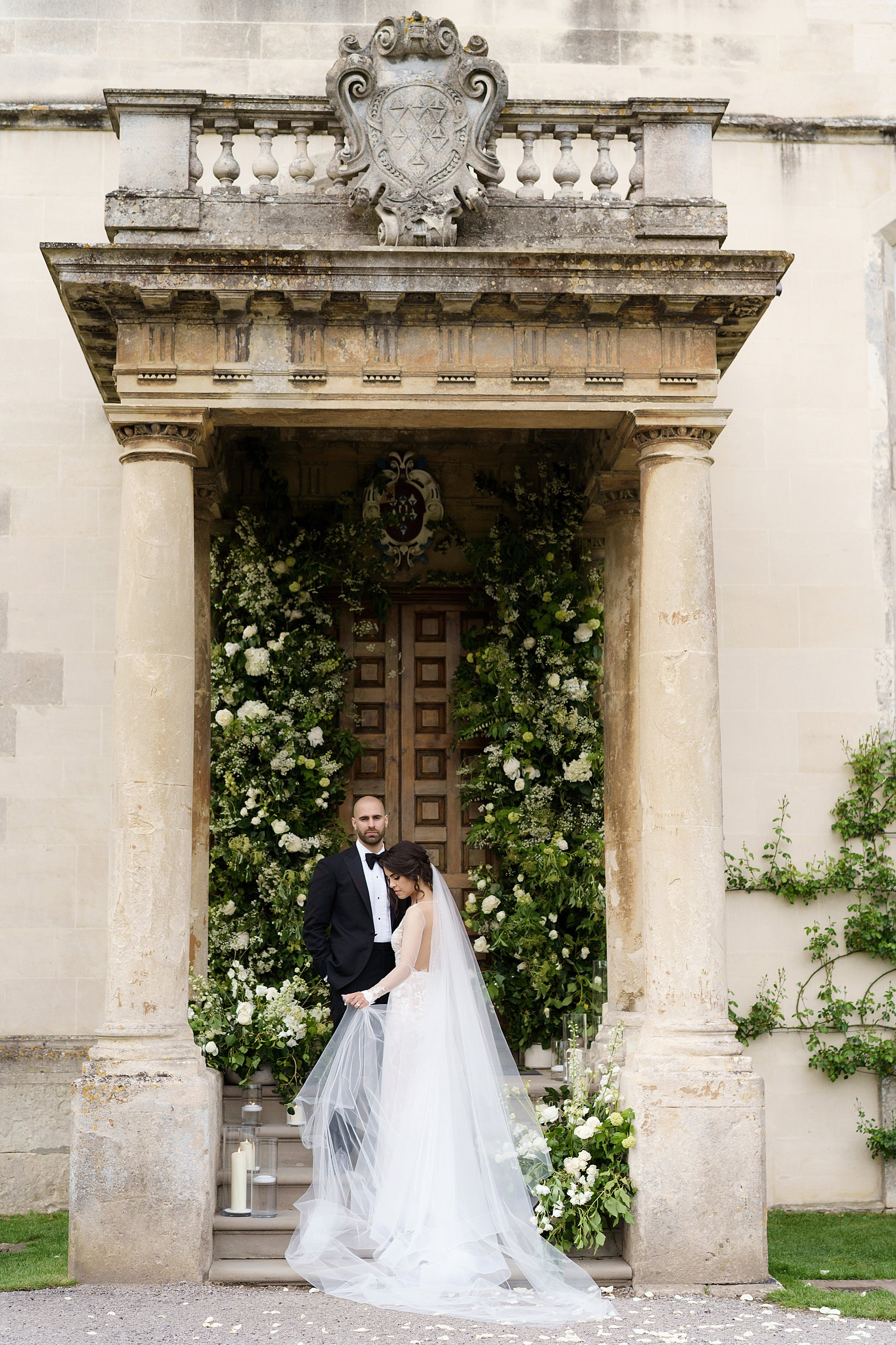 bride and groom stand under porch with columns against backdrop of huge statement greenery and white floral arrangement for a micro wedding