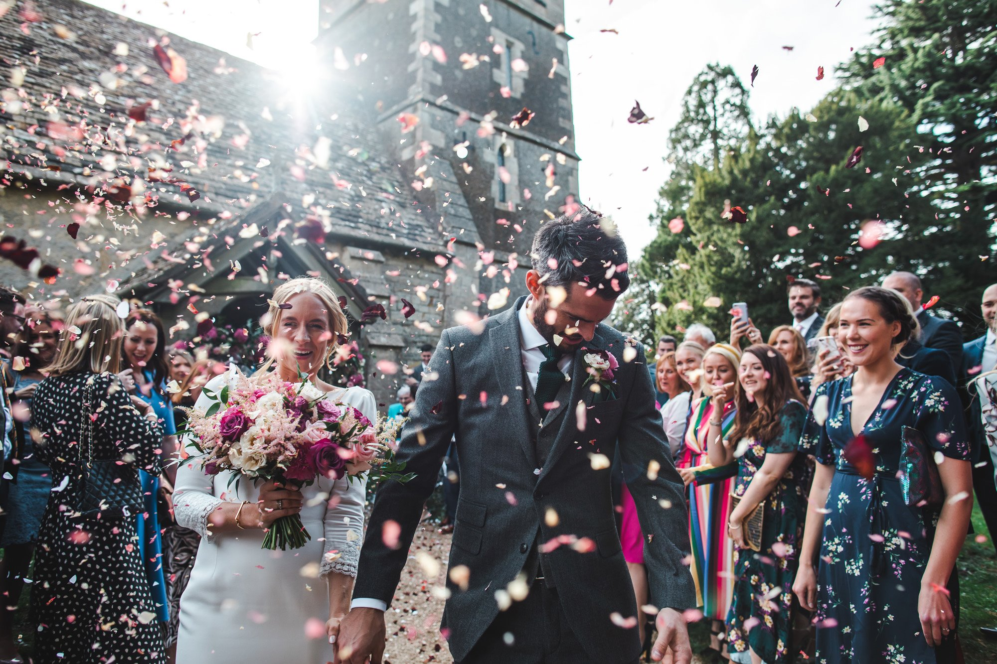 Explosion of rose petal confetti as happily newlywed couple leave Elmore church in Gloucestershire just after their marriage ceremony