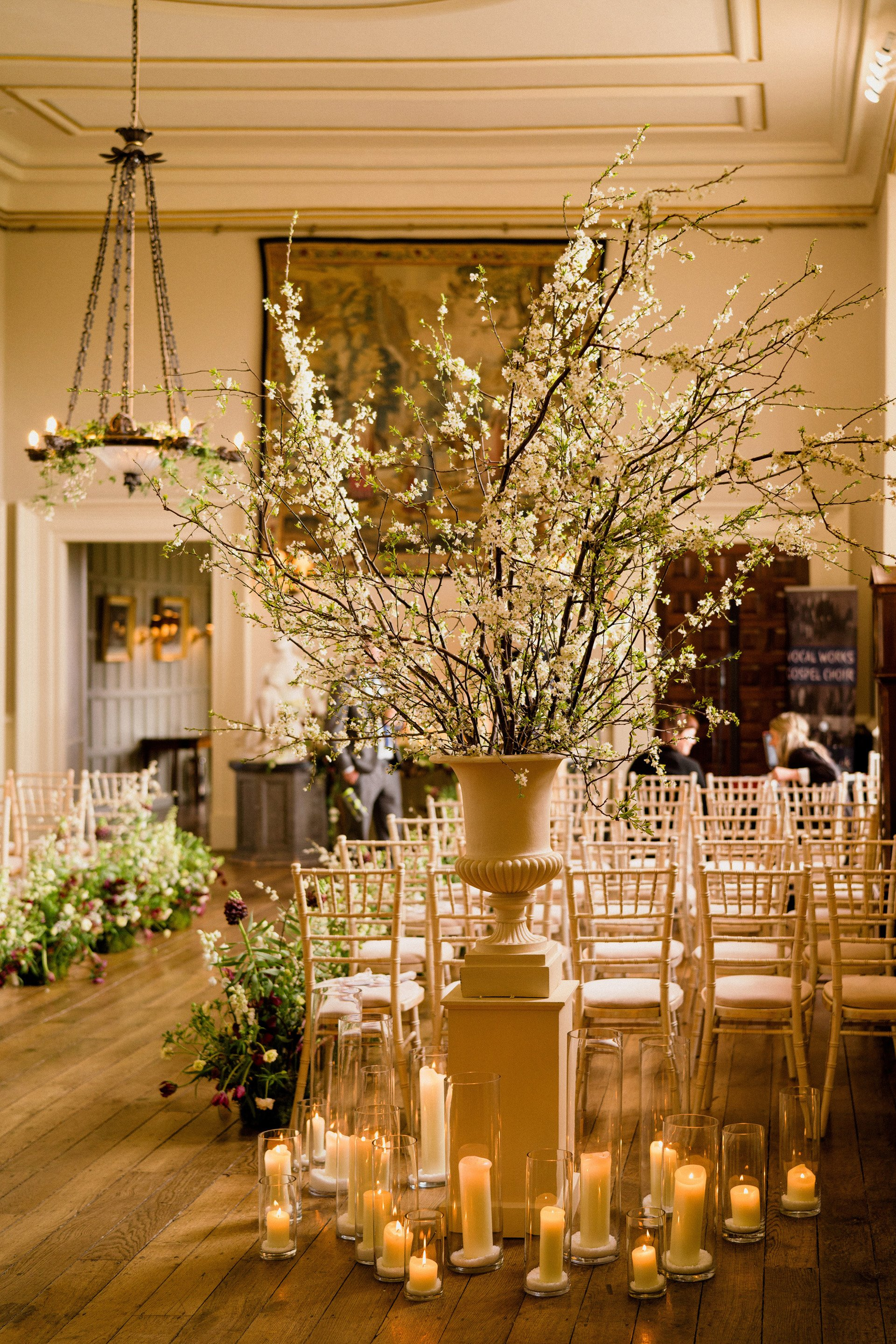 Spring wedding decor with candles and spring branches in urns in a stately home hall in the Cotswolds