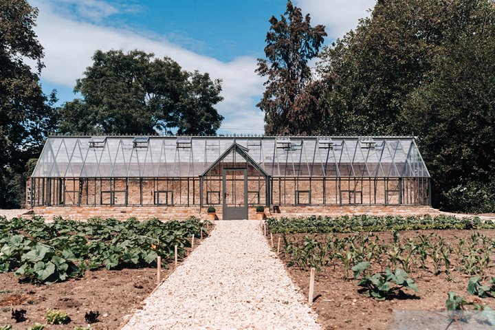 The new greenhouse at Elmore Court sitting proudly in the 700 year old walled garden surrounded by organic seedlings popping up fresh for sustainable wedding menus as soon as covid allows