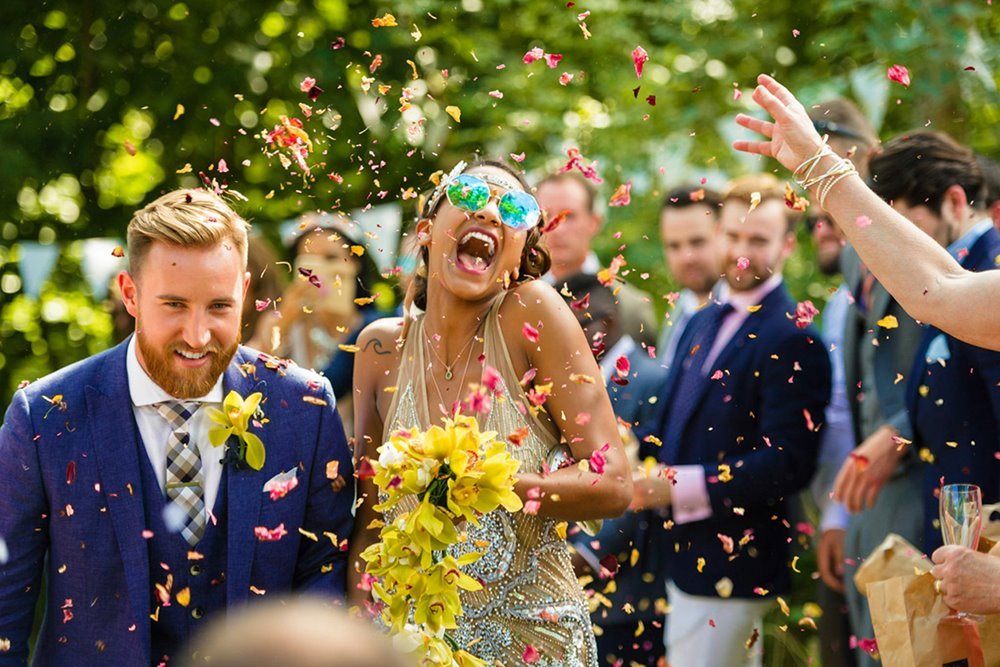 Festival bride wearing sunglasses and holding a yellow bouquet throws back her head and laughs in an explosion of confetti as her newlywed husband keeps his head down