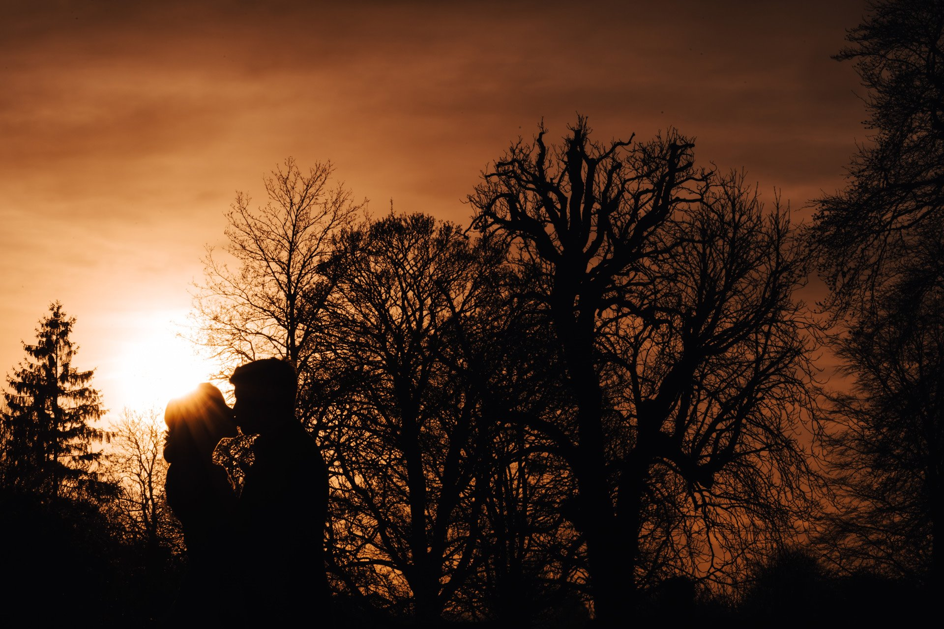 Newlywed couple kiss against an orange sunset sky at Elmore Court