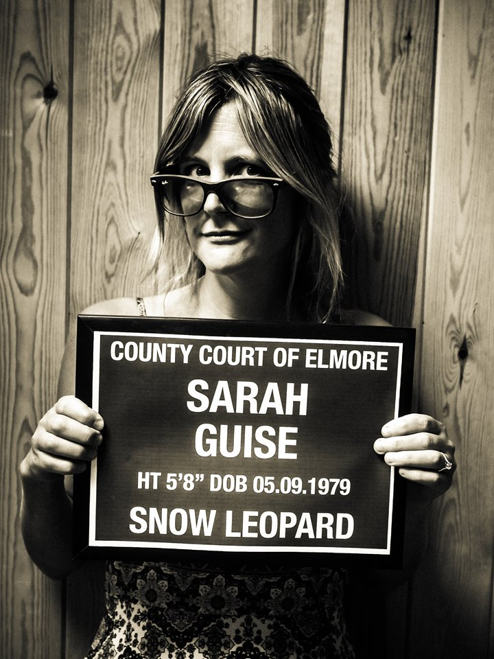 Anselm Guise's wife Sarah of stately home Elmore Court pictured in funny black and white mugshot photo holding up joke sign