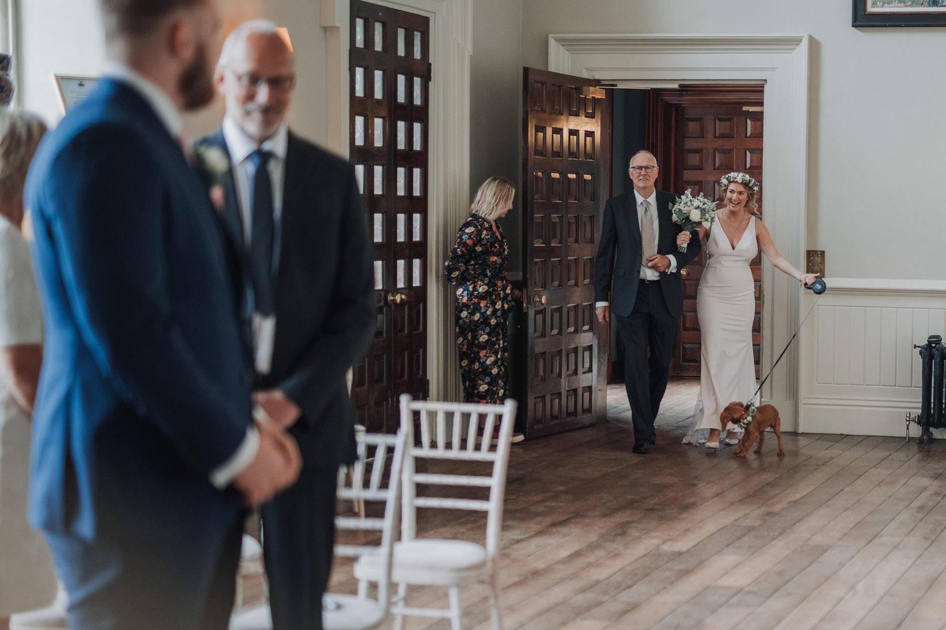 Here comes the bride with puppy bridesmaid wearing flowers at elmore court covid micro wedding