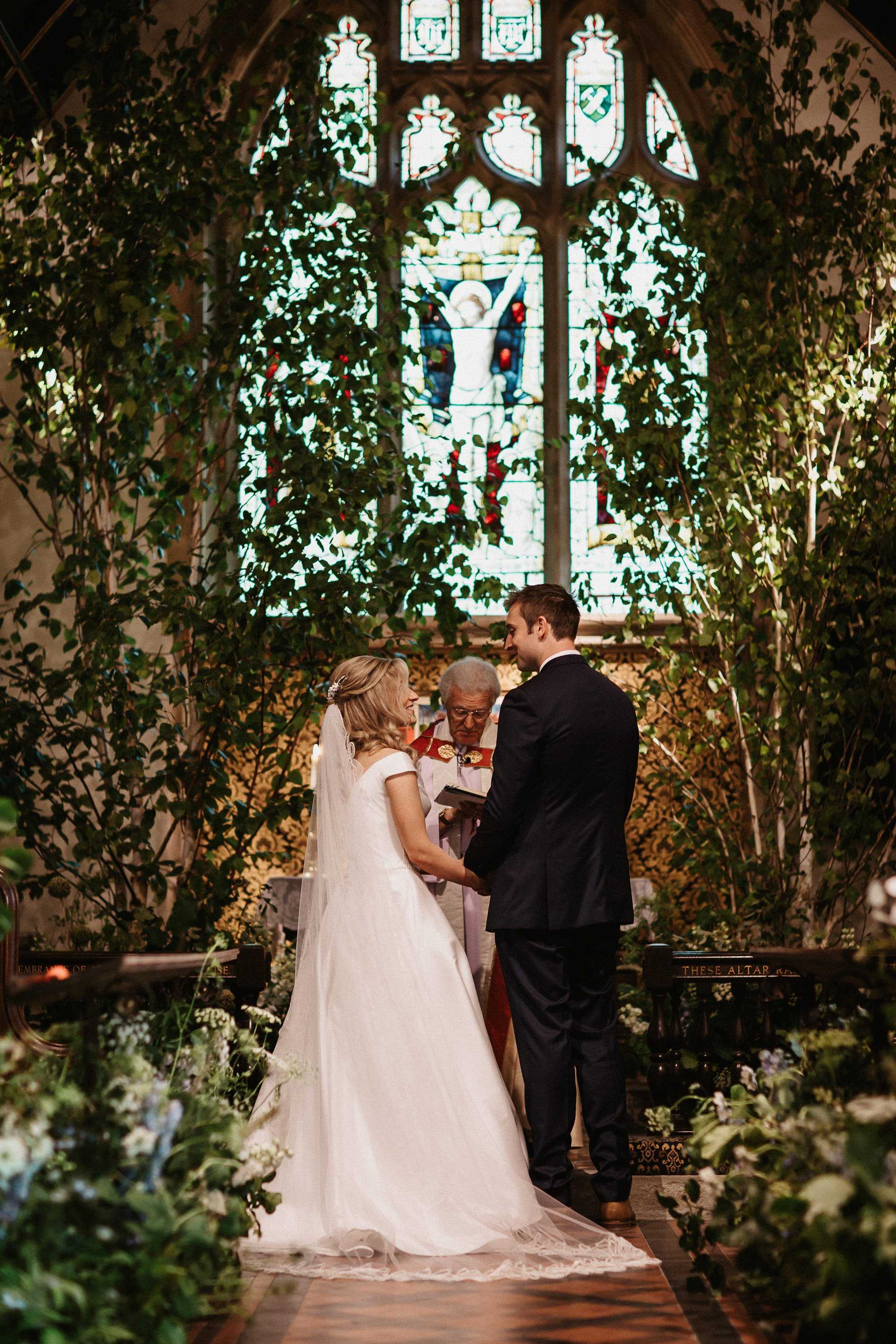 Beautiful english church wedding ceremony at Elmore church in Gloucestershire decorated with trees
