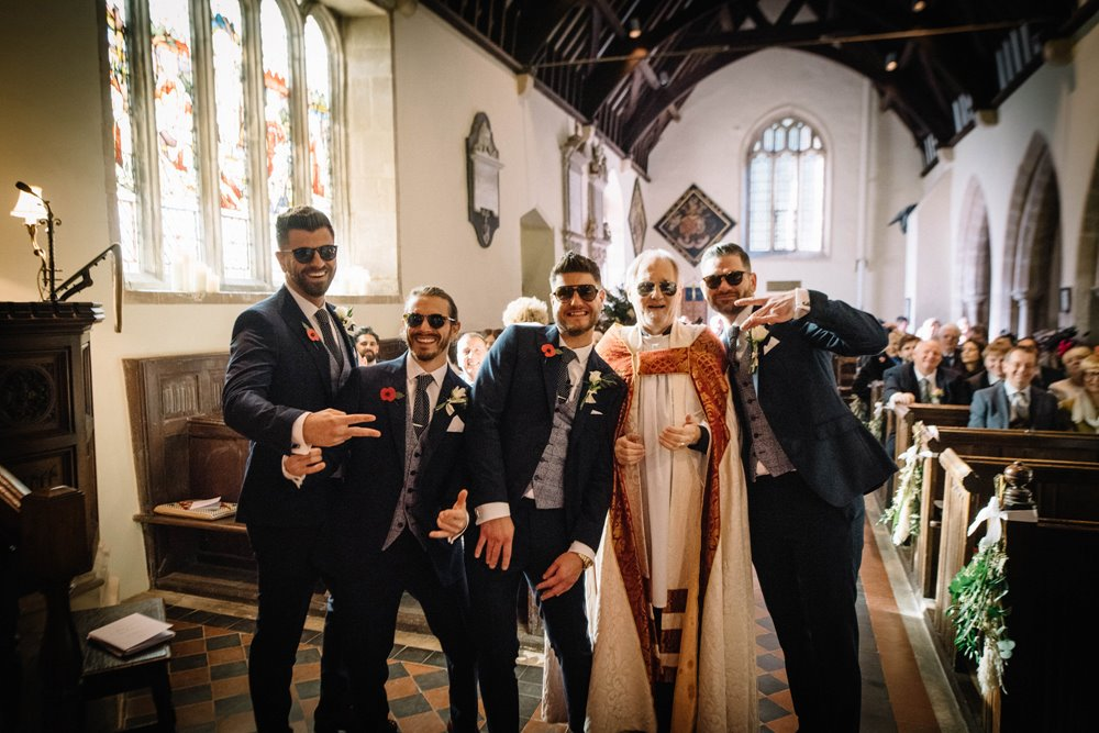 Groomsmen in sunglasses pose with the Vicar of St John the Baptist church at a relaxed church wedding in Elmore