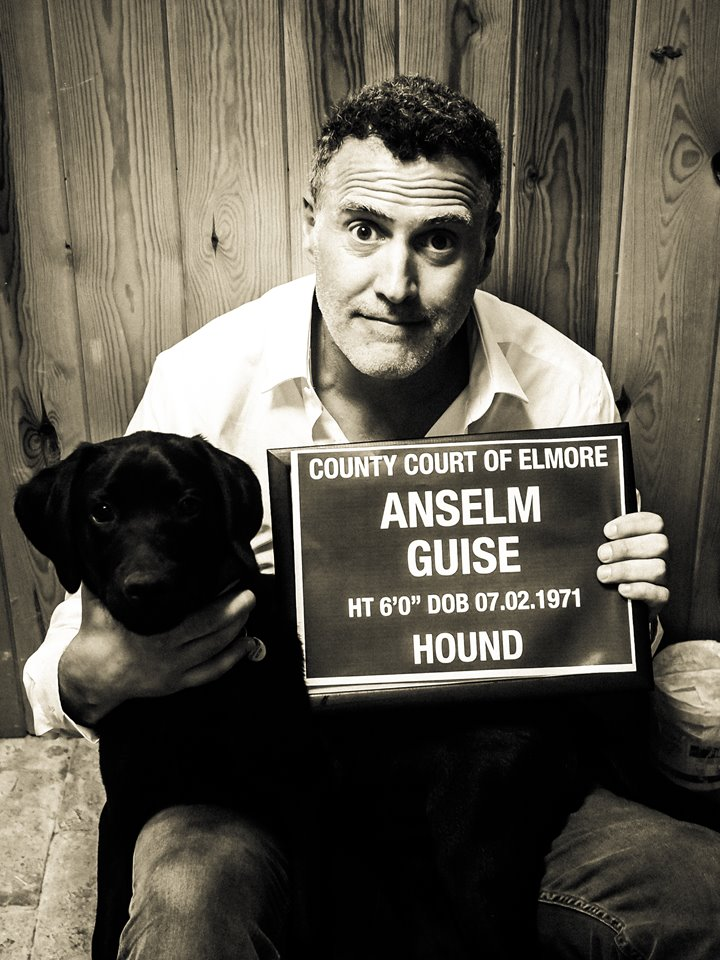 Anselm Guise of mansion house Elmore Court with his dog Charlie, holding up a joke mugshot sign for the Team E page of wedding planning site