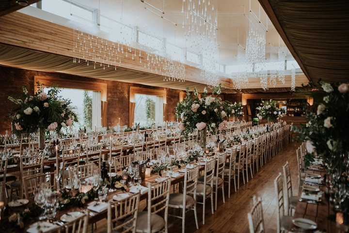 A festival wedding banquet in The Gillyflower at Elmore Court, long banqueting tables are laid with candles, tall flower arrangements and a beautiful twinkling light showers hangs from the ceiling