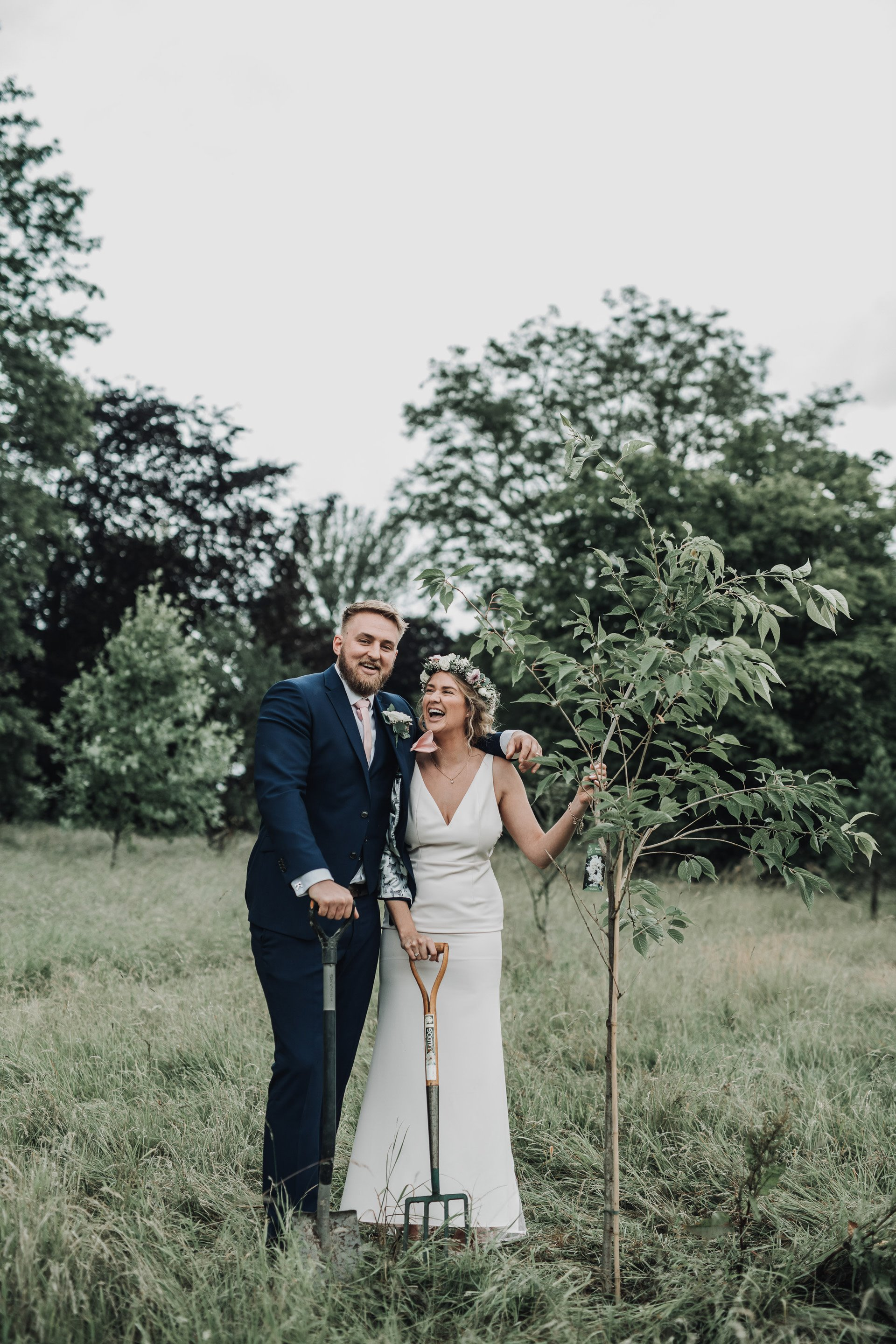 Bride and groom stand with the tree they just planted as part of their micro wedding ceremony during corona pandemic at sustainable wedding venue elmore court in cotswolds