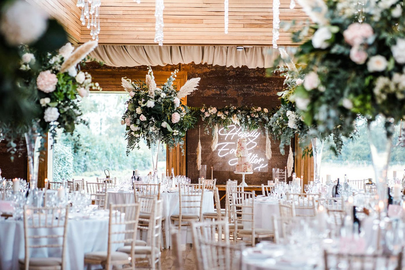 Pretty pink and greenery wedding reception with round tables and foliage pampas grass floral arrangements, neon sign back lighting the cake table