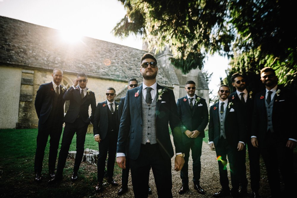 Groomsmen in sunglasses and suits looking very cool outside Elmore church before a wedding ceremony in Gloucestershire