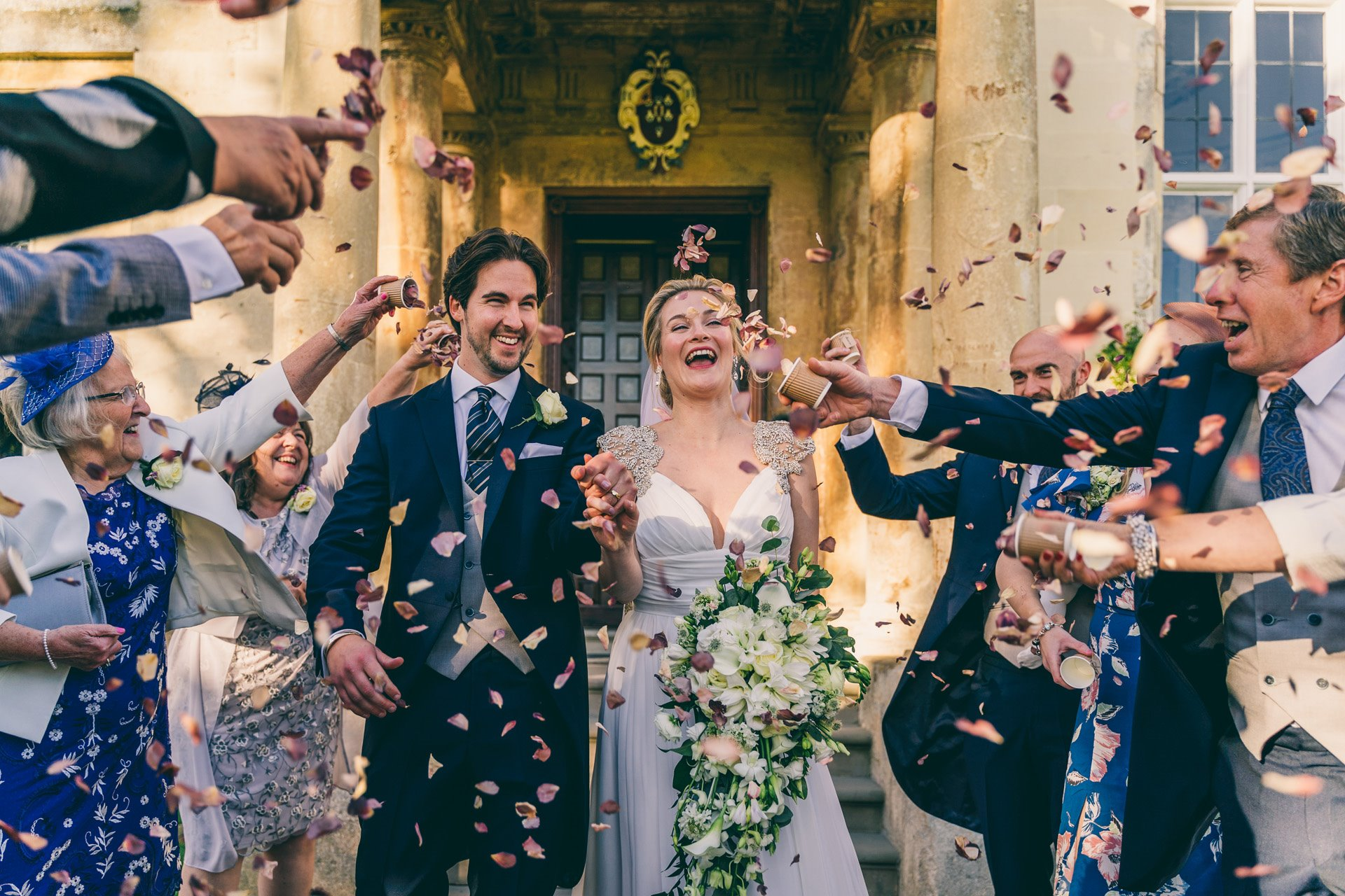 Micro wedding couple covered in confetti surrounded by friends and family outside at elmore court covid safe wedding venue
