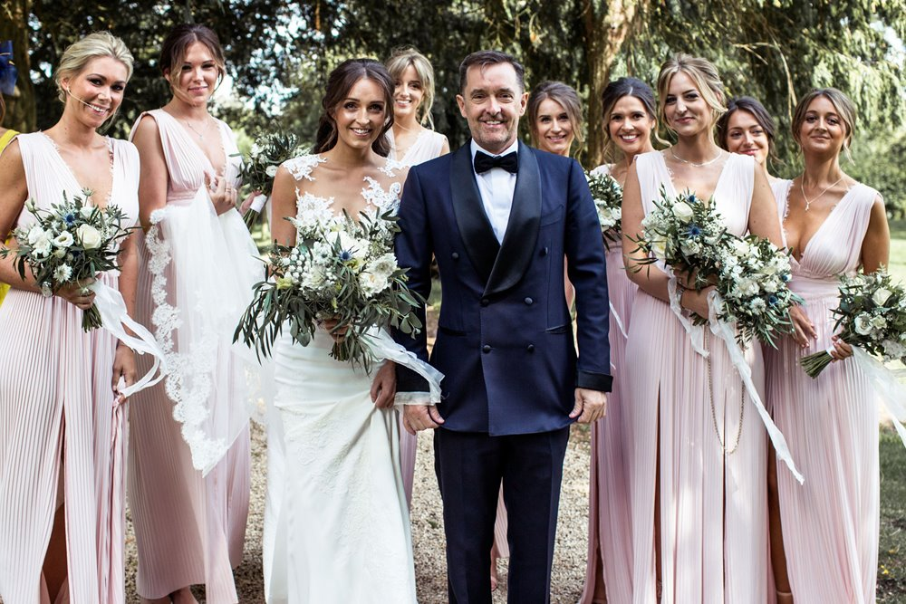 Bride and groom and bridal party pose with bouquets in the prettiest churchyard in England at Elmore Church