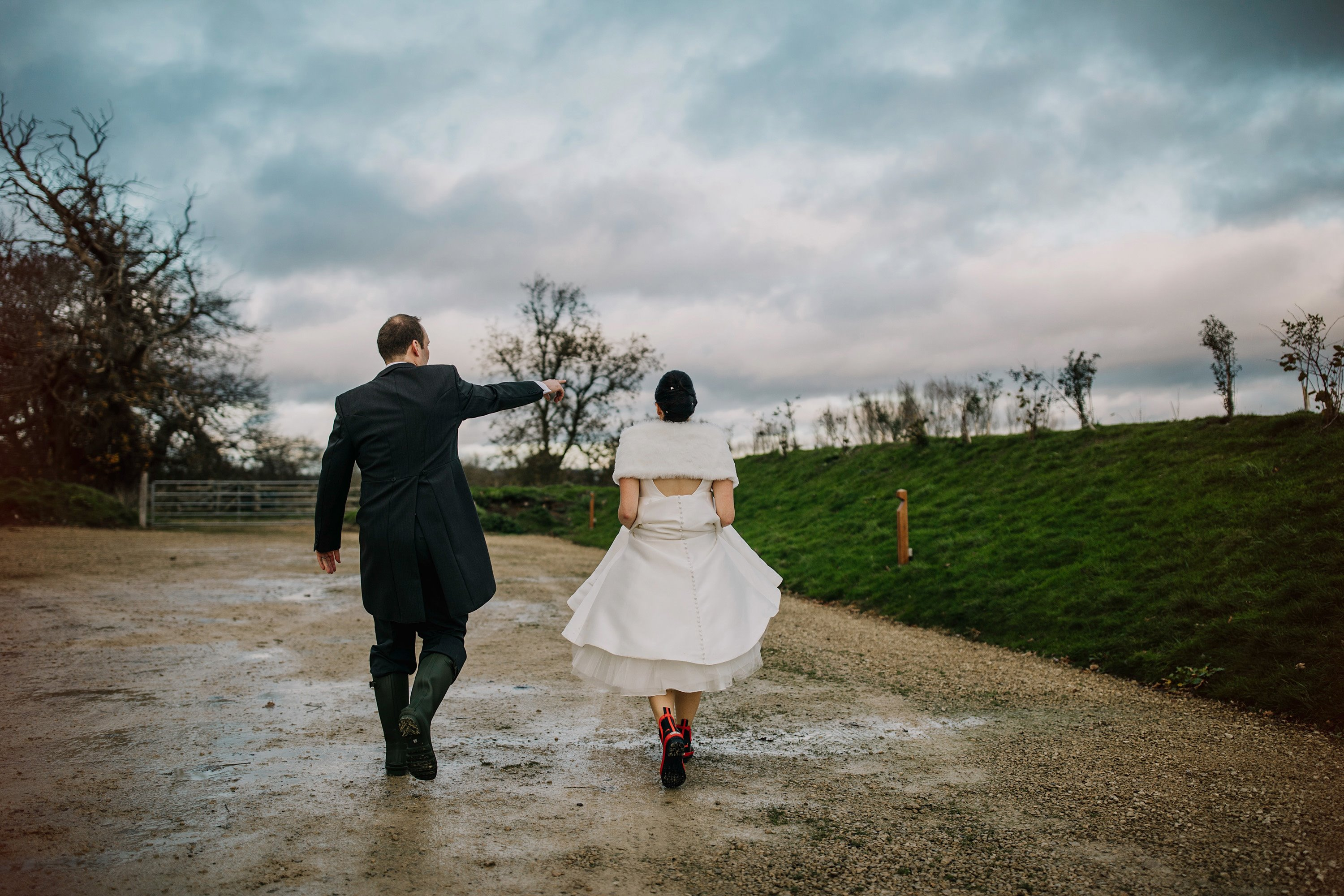 Bride wearing wellies and shawl on a rainy day