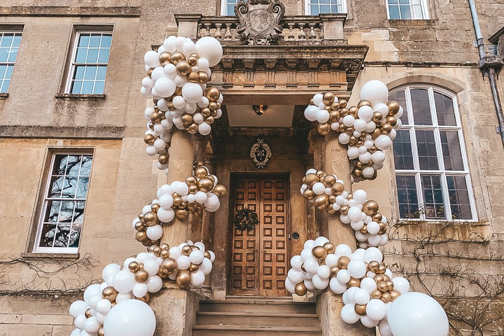 Wedding balloon installation in gold and white on the steps of a stately home for a wedding fair in Gloucestershire