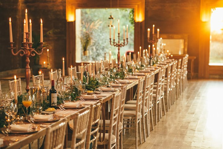 Candlelit Micro wedding reception dinner with banqueting table and candelabras