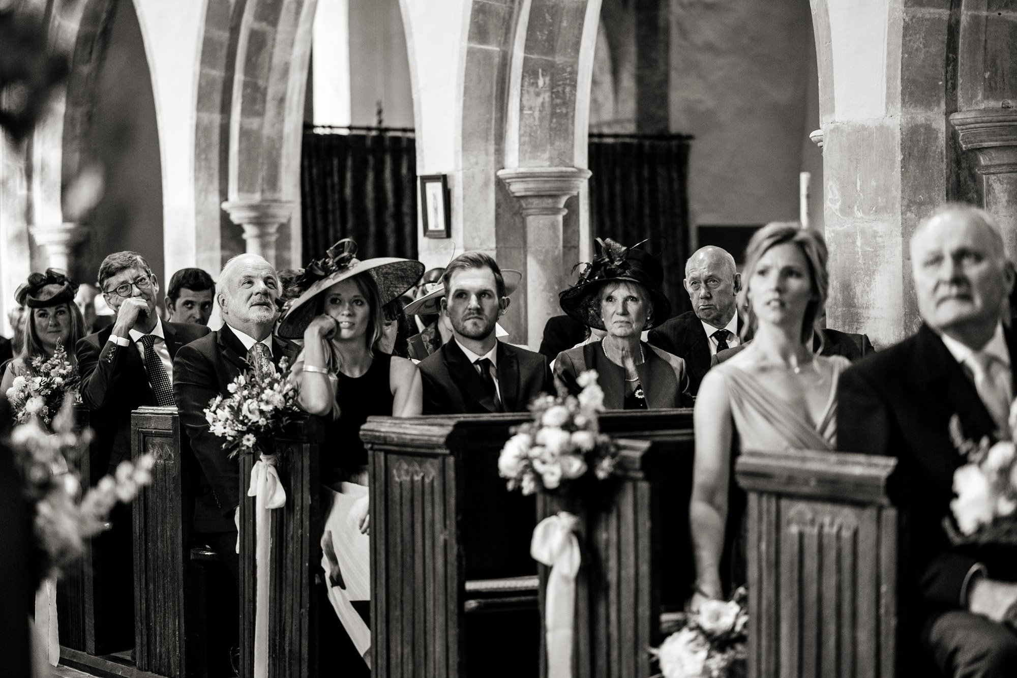 Black and white photo os Wedding guests in pews at a church wedding at Elmore