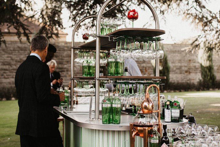 Outdoor gin bar in beautiful green ombre with copper details stationed under the cedar tree for a cool outdoor wedding reception at Elmore Court