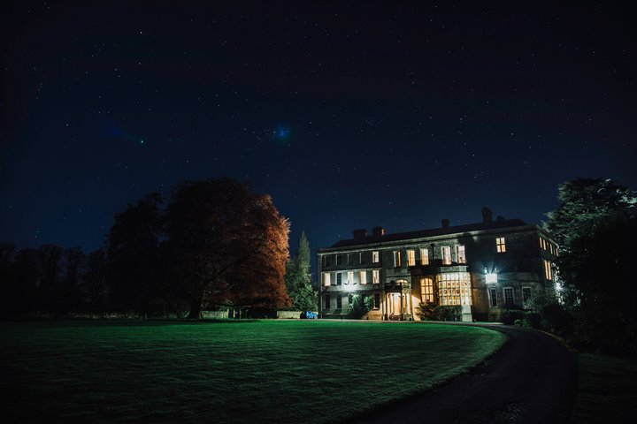 Glowing stately home Elmore Court at night. The huge beech tree to the left of the grade two listed house is slightly lit up by the light from the windows