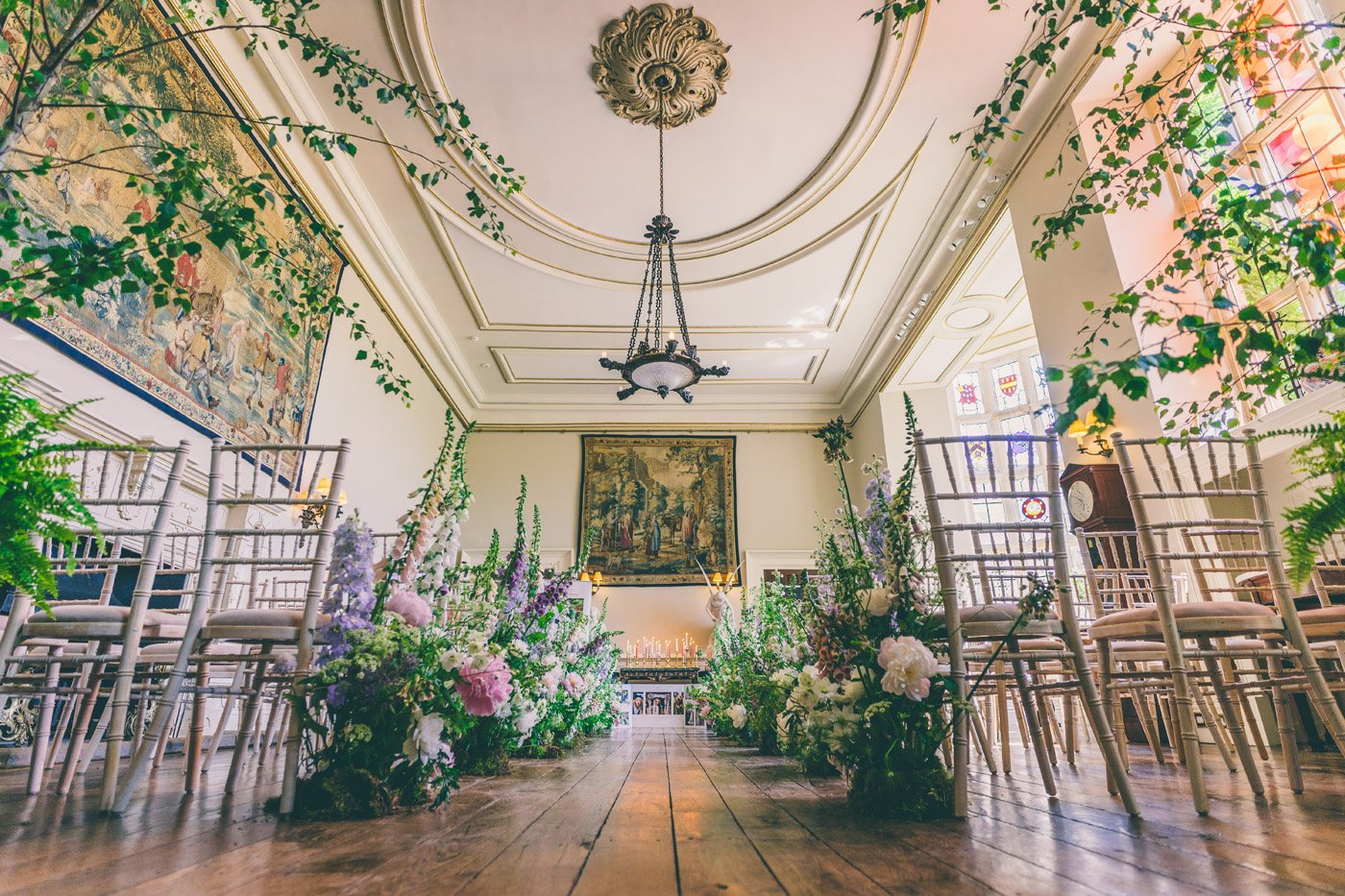 Stunning floral wedding aisle with tall wildflower arrangements and trees flanking the wedding aisle in the ceremony hall at Elmore Court in Gloucestershire