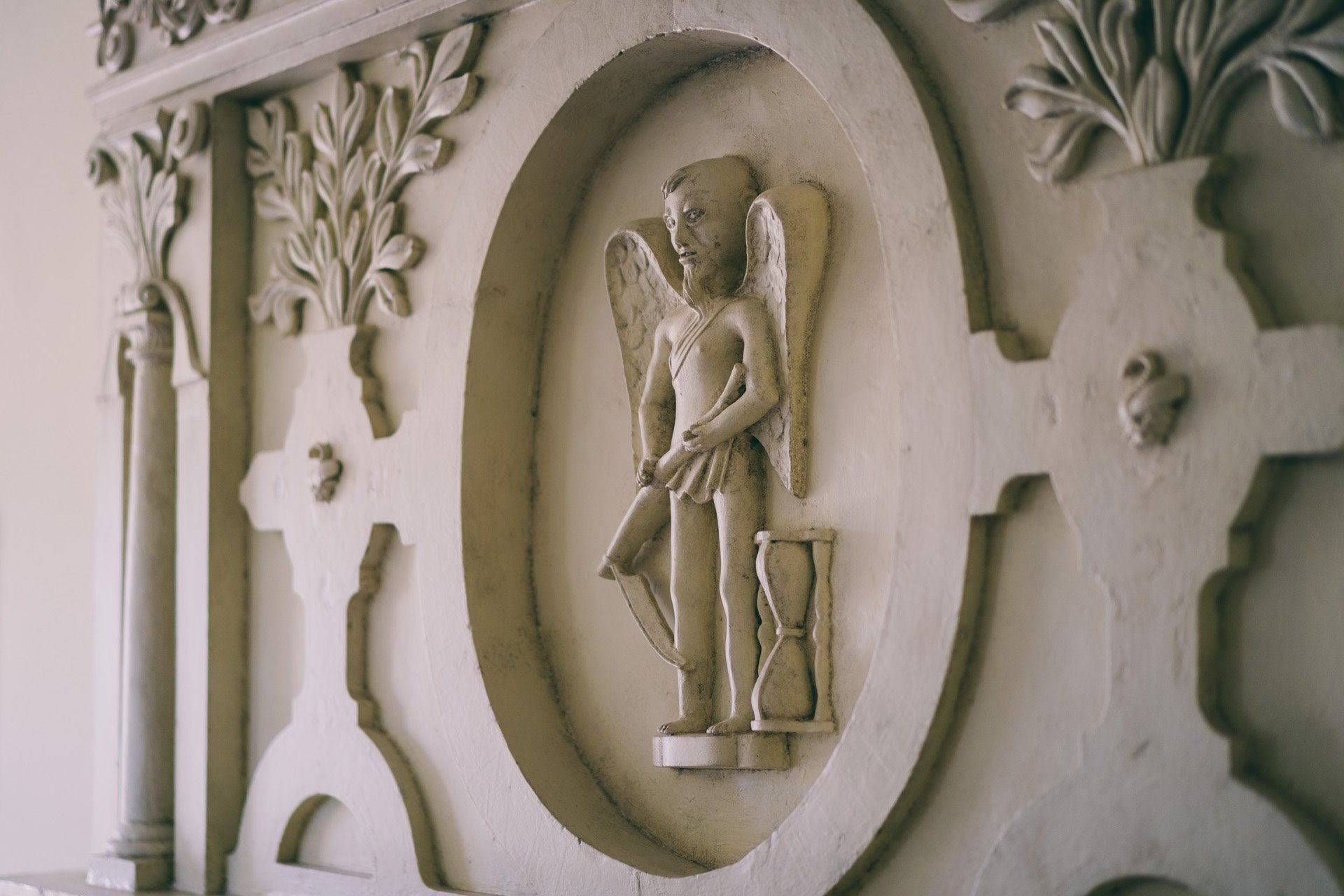 Depiction of Father Time with scythe and hourglass in the fireplace of the time bedroom at wedding venue Elmore Court in Gloucestershire